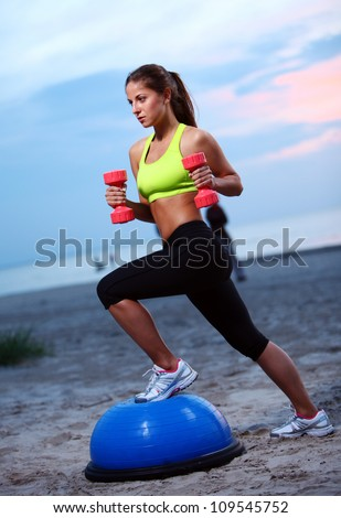 Woman doing fitness exercises with bosu ball on the beach