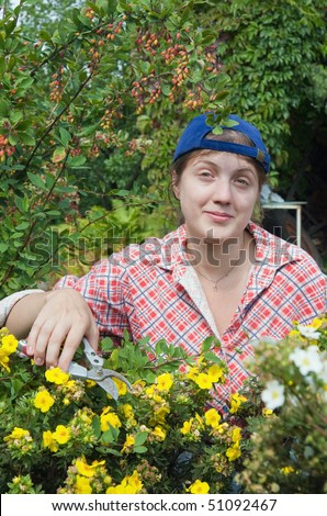 Woman doing garden work cutting the  prairieweed  at beautifully sunny day