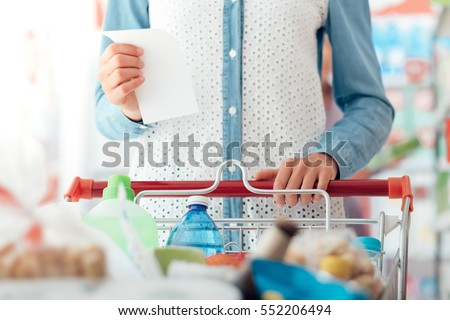 Woman doing grocery shopping at the supermarket, she is pushing a cart and checking a list