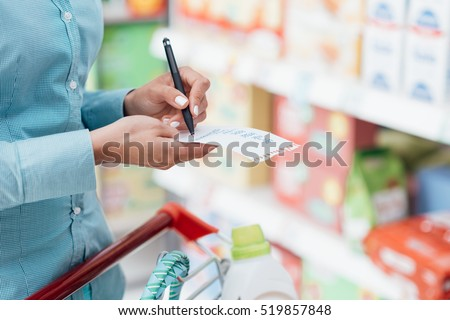 Woman doing grocery shopping at the supermarket, she is pushing a cart and checking items on a list