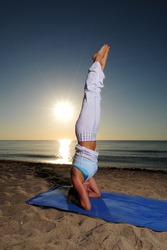 Woman doing headstand yoga pose on beach during a beautiful sunrise