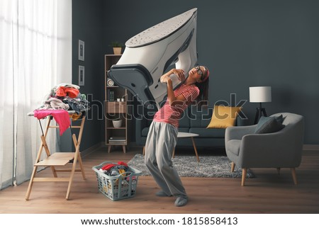 Woman doing household chores and holding a huge heavy iron, stress and housework concept Stock photo ©