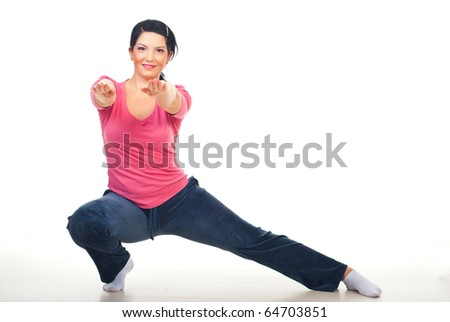 Woman doing lateral lunge and standing with hands outstretched on floor over white background