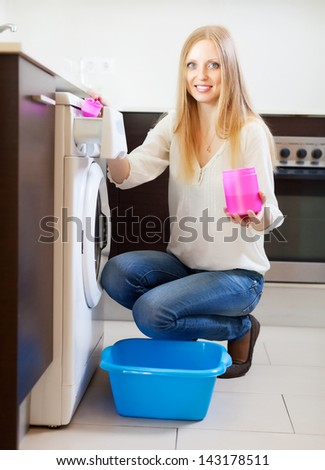 woman doing laundry with detergent at home - stock photo