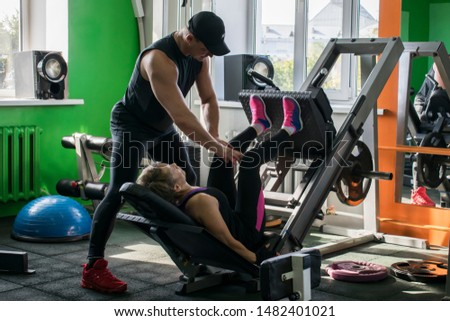 Woman doing leg press with a weight trainer. Training with a trainer.