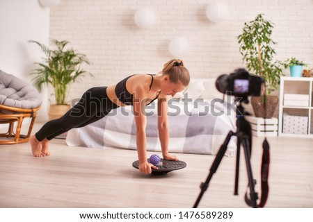 woman doing plank exercises on a special simulator balancer. blonde sports clothes, home exercise Strengthens your muscles.the girl keeps balance balancing on sports equipment.writes a video blog