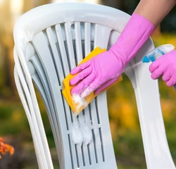 woman doing plastic chair cleaning with spray foam, close-up