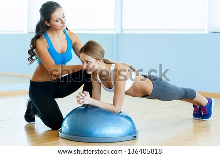 Woman doing push-ups. Beautiful young woman in sports clothing doing push-up with her personal instructor