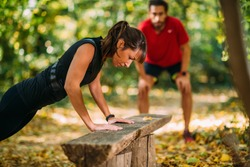 Woman doing push-ups in the park with personal trainer