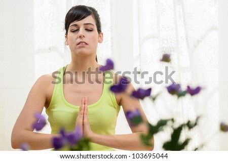Woman doing relax yoga exercising at home. Meditation and concentration indoors. Beautiful caucasian model.