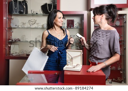 woman doing shopping at the jewellery store and paying by credit card
