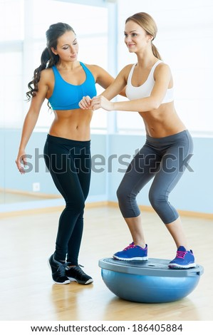 Woman doing sit-ups. Beautiful young woman in sports clothing doing sit-up with her personal instructor