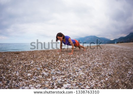 Woman doing sports on the beach. Push up. The girl does sports exercises on the background of the sea and mountains. Brunette does exercises for press. Active lifestyle. Warming up before running. #1338763310
