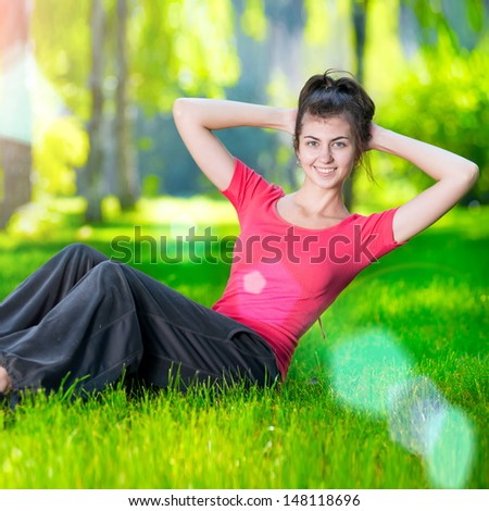 Woman doing strength exercises for abdominal muscles at outdoor sport exercise. Smiling happy doing yoga stretches after running. Fitness model outside in green park  on summer day.