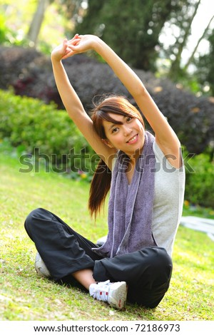 woman doing stretching exercise in park