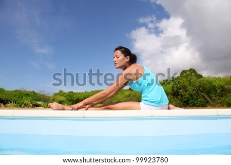 Woman doing stretching exercises by a pool