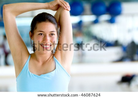 Woman doing stretching exercises for her arm and back at the gym