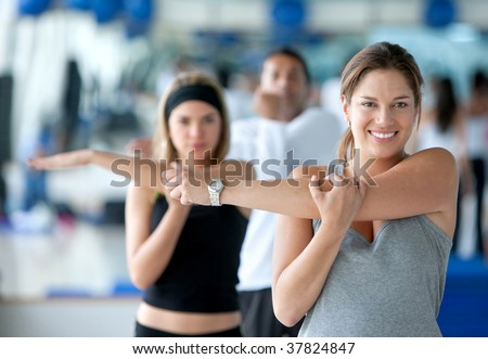 Woman doing stretching exercises for her arm at the gym - stock photo