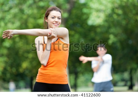 Woman doing stretching exercises in a class outdoors