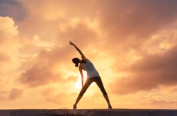 Woman doing stretching warm up exercise outdoors against a beautiful sunset.