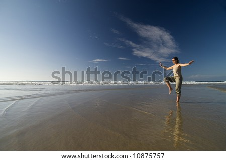woman doing tai chi by the seashore in a sunny day