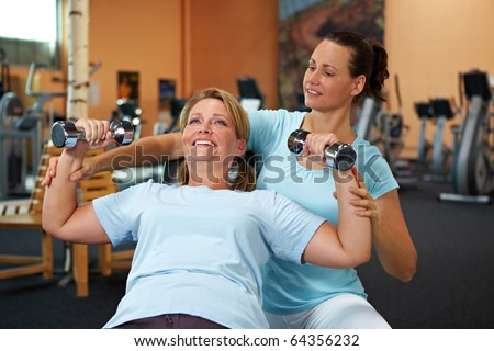 Woman doing weight training with female fitness coach