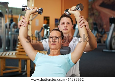 Woman doing weight training with fitness coach