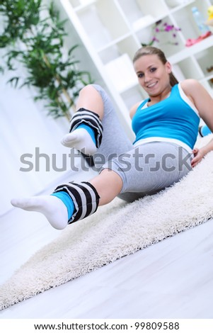 woman doing workout with legs weights, focus on weights