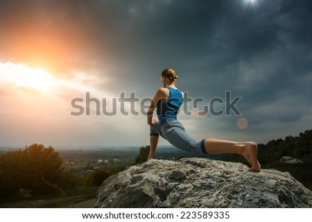 Woman doing yoga against the setting sun. Fitness classes outdoors. Stormy sky with sunshine. Attractive fitness woman, lifestyle portrait, caucasian model