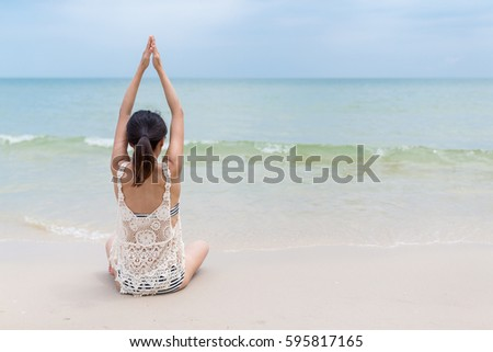 Stock Photo Woman doing yoga at sand beach