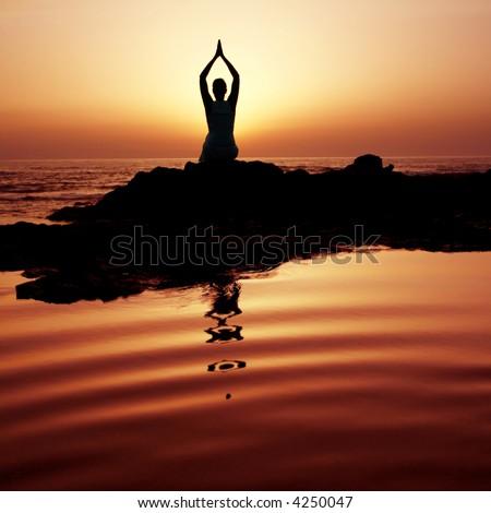 Woman doing yoga at sunset on the seashore