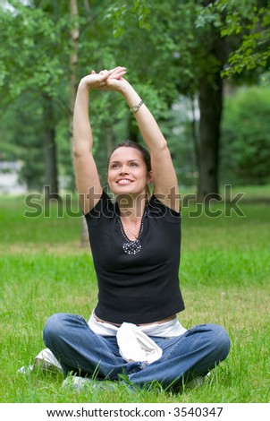 Woman doing yoga exercise on a fresh grass in a park