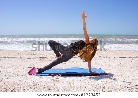 woman doing yoga exercise woman doing yoga exercise  Salamba Kapotasana or Supported Pigeon Pose on an empty beach at the gulf of mexico in bonita springs floridawith long hair blowing in wind