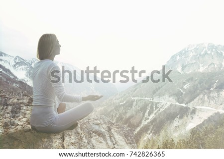 woman doing yoga exercises over the top of a mountain