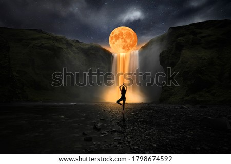 Woman doing yoga in front of a magic waterfall Stock photo ©