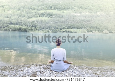 woman doing yoga in front of a spectacular mountain lake