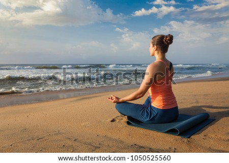 Woman doing yoga - meditating and relaxing in Padmasana Lotus Pose outdoors at tropical beach on sunset