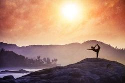 Woman doing Yoga natarajasana dancer pose on the rocks at sunset at Om beach, Gokarna, India