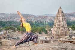 Woman doing yoga near Virupaksha temple in Hampi, Karnataka, India
