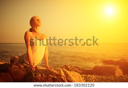 woman doing yoga on the beach by the sea at sunset