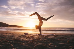 Woman doing yoga pose handstand with splits on the beach with sunset in background. Female exercising yoga on the sea shore.