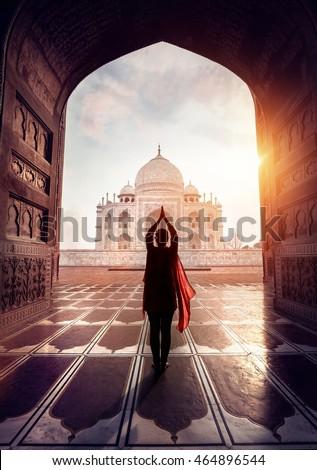 Woman doing yoga tadasana tree pose with flying red scarf in silhouette near Taj Mahal in Agra, Uttar Pradesh, India