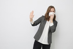 Woman don't want to get Corona virus covid-19 / 2019-ncov and is trying to keep a distance saying stop with her hand while holding a protection face mask to avoid infection