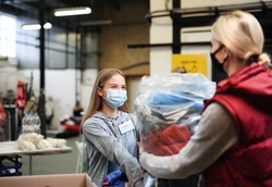 Woman donating clothes community charity donations center, coronavirus concept.
