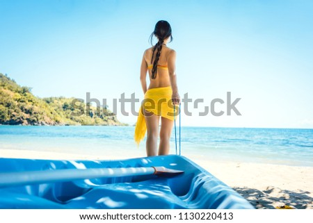Woman dragging her boat to the water on the beach for watersports