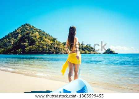 Woman dragging her boat to the water on the beach for watersports #1305599455
