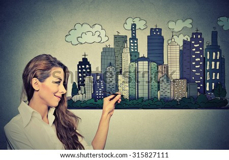 Woman drawing city skyline on grey wall background. Real estate development, house market economy, investment opportunity