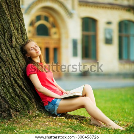 Woman dreaming by the tree with a book. Pretty student girl is sitting near the tree with a book relaxing with joyful and relaxed expression in the university campus. Summer days concept.