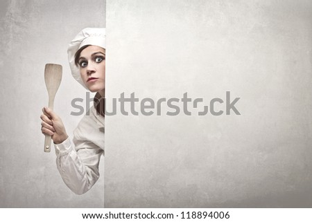 Woman, dressed as a cook, showing a wooden spoon