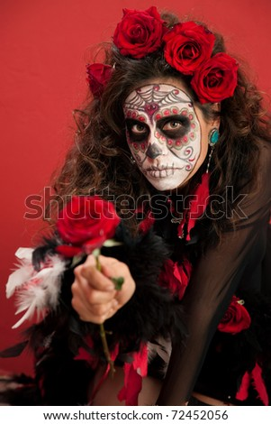 Woman dressed for All Souls Day holding out a red rose